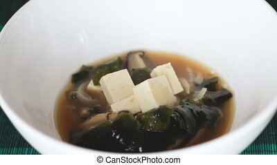 Macro shot of miso soup in white bowl - Close up of japanese...