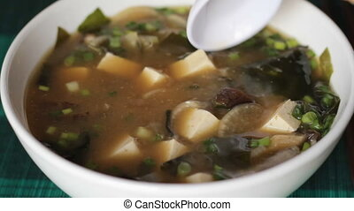 Stirring miso soup with white spoon macro shot - Close up of...