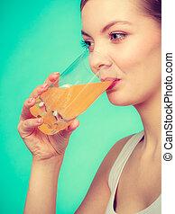Woman drinking orange flavored drink or juice - Food, health...