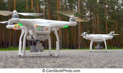Two quadcopters on the asphalt, forest background. - Two...