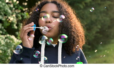 African American girl teenager or young woman blowing...