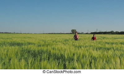 Mom plays with her daughter in a field of wheat.