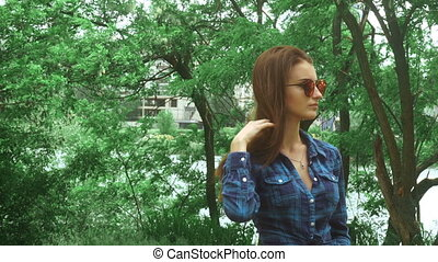 young woman in mirror sunglasses and blue shirt touching her...