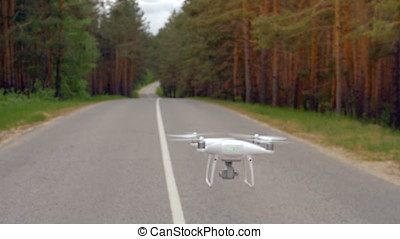 A quadcopter flying along the asphalt road. - A quadcopter...