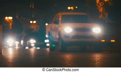 Night Traffic in the City. Defocused Cars Drive with Lights...