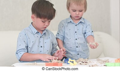 Two little kids playing with dough and learning how to bake