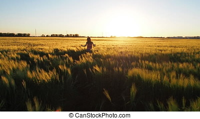 Girl in a wheat field at sunset.