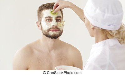 Cosmetologist Care for the skin of the face young man. man receiving a facial treatment application