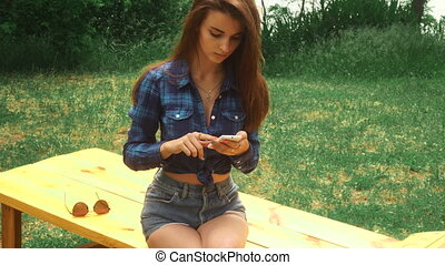 adorable young brunette woman using a mobile phone at the park on a bench