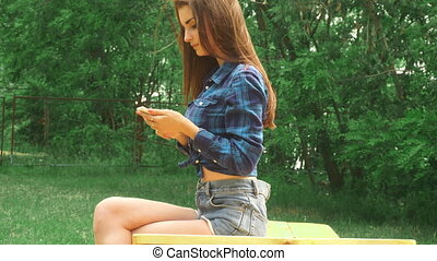 young girl sits on a bench at the park and using a mobile phone