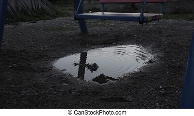 Abandoned children's playground, innocence sad child swinging on a swing. reflection in puddles.