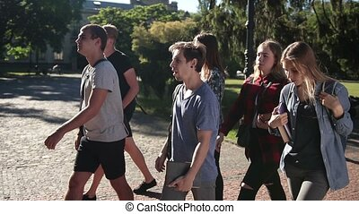 Group of students going to lecture in university - Happy...