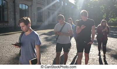 Students busy with smartphones on univesity campus -...