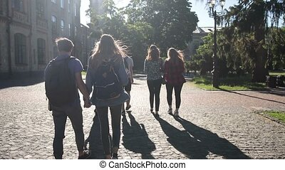 Group of college students walking outdoors - Back view of...