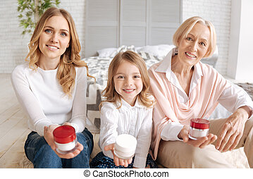 Girl, mother and grandmother holding jars of cream - Here...