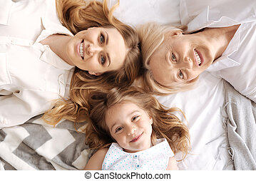 Charming three females of different age lying head to head -...