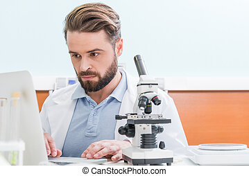 concentrated bearded scientist working with microscope and laptop in laboratory