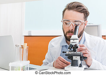 concentrated bearded scientist working with microscope in laboratory