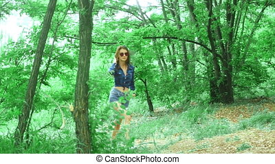 young sexy brunette walks at the park in small jeans shorts...
