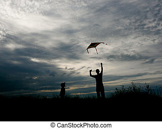 man and small kid flying a kite at sunset - man and small...