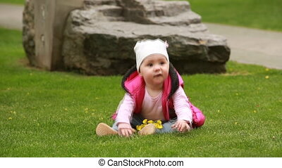 Cute smiling baby-girl crawling on a green grass in the city...