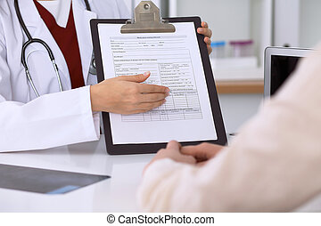 Close up of a female doctor pointing into an application form while consulting patient