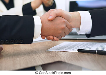 Close up of business people shaking hands at meeting or negotiation in the office. Partners are satisfied because signing contract