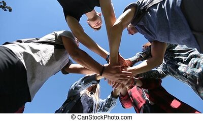 Team of friends showing unity joining hands - Closeup pile...