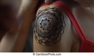 Woman gets henna tattoo on her shoulder - Closeup video of...