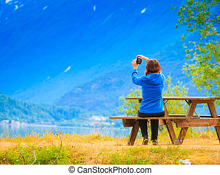 Tourist taking photo at norwegian fjord - Tourism and...