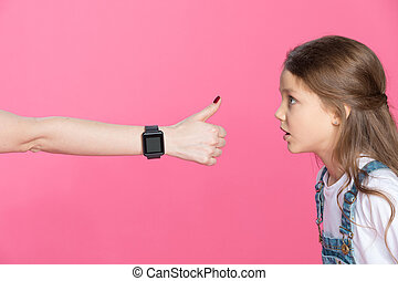 Side view of shocked little girl looking at woman with smartwatch showing thumb up