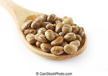 Roasted soybeans (soy nuts) in wooden spoon isolated on...