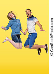 Portrait of a young couple jumping against yellow background...