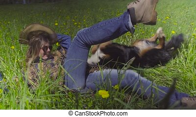 Young woman and a dog in the grass