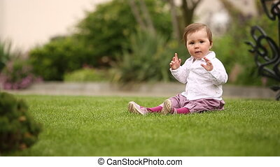 Little beautiful pretty baby-girl sitting on the green grass...