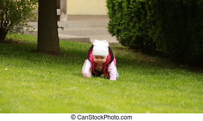Cute little baby-girl is crawling in the green fall-meadow...