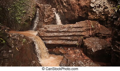 A noisy multistage waterfall falling from a rocky cliff....