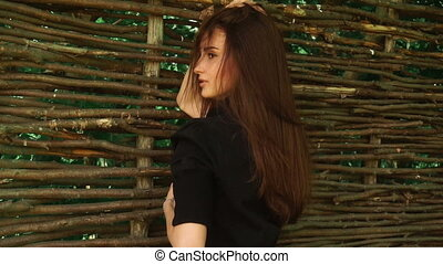 sensual young woman stands at the fence and touching her...