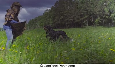 Young woman and a dog running on a field - Young woman and a...