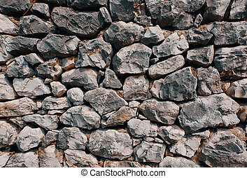 old stone wall consisting of stacked naturally shaped loose rocks - background pattern