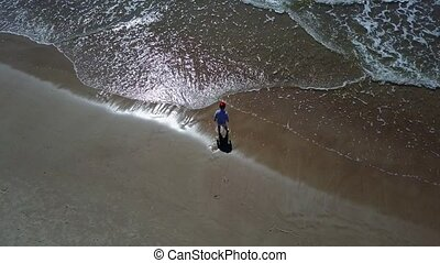 Little Boy playing with Sea Aerial drone top view 4K UHD...