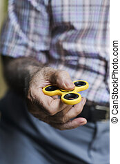 old man playing with a fidget spinner - closeup of an old...