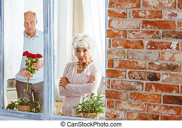 Man apologizing to woman - Senior man with flowers...