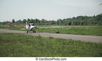 A small white plane is moving along the runway. The propeller is spinning