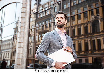 Young serious man in jacket holding laptop computer while...