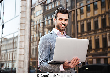 Portrait of a young handsome man in jacket holding laptop -...