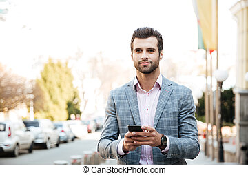 Concentrated young businessman outdoors chatting - Picture...