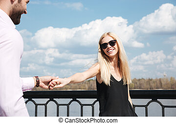 Young happy woman holding her man hand while walking - Young...