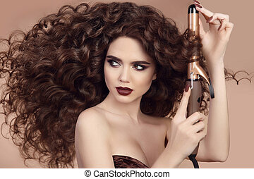 Curly Hair. Hairstyling. Beautiful Brunette Woman portrait...