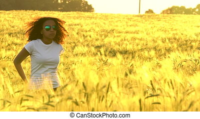 African American girl teenager young woman in field of wheat or barley at sunset or sunrise
